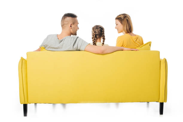back view of parents and daughter sitting on yellow sofa isolated on white stock photo