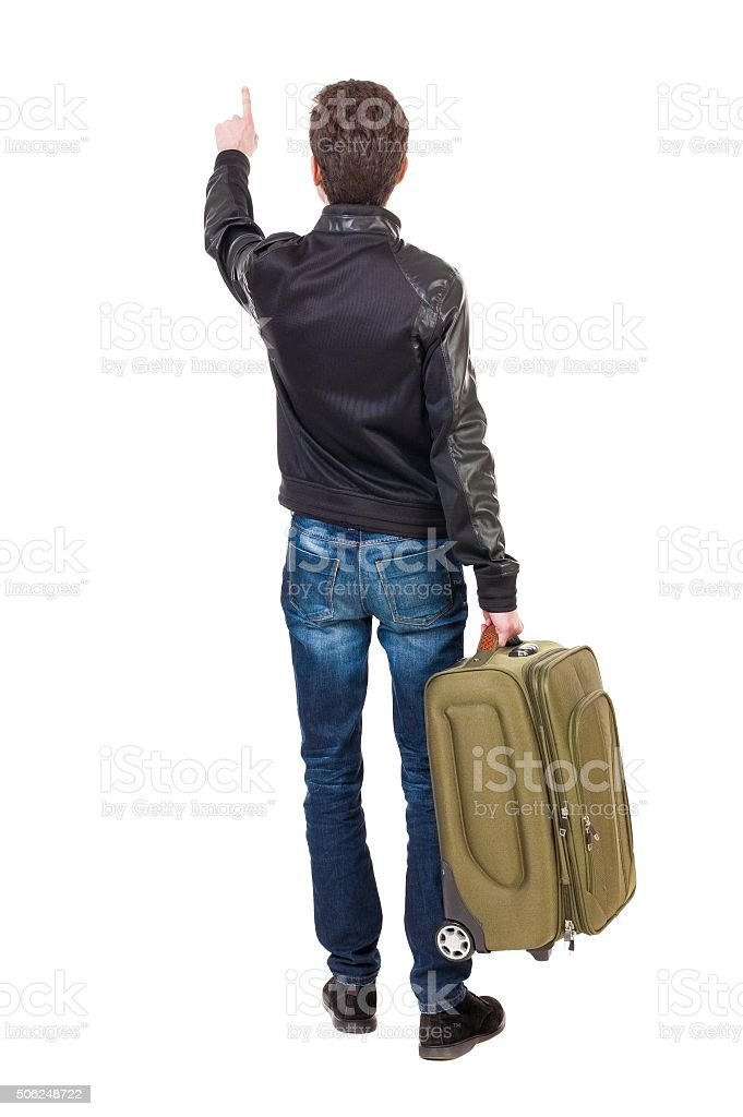 back view of  pointing man  with suitcase. stock photo