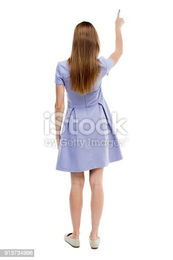 istock Back view of  pointing woman. 913734996