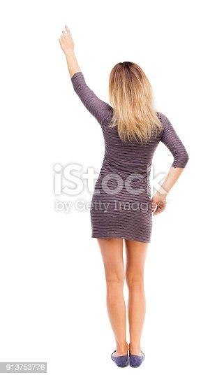 istock Back view of  pointing woman. 913753776