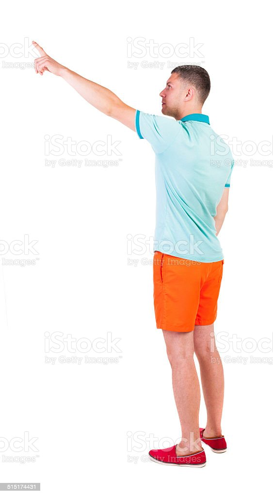 Back view of  pointing young men in  t-shirt and shorts. stock photo