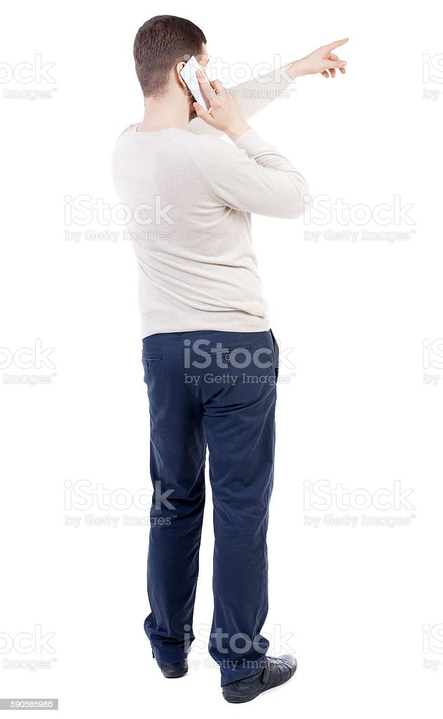 Back view of  pointing young men talking on cell phone. stock photo