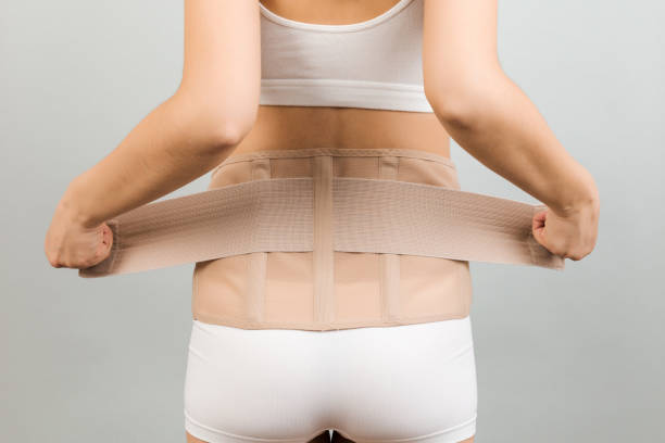 Back view of pregnant woman in underwear dressing orthopedic corset to make the backache go away at gray background with copy space. Close up of orthopedic abdominal support belt concept stock photo