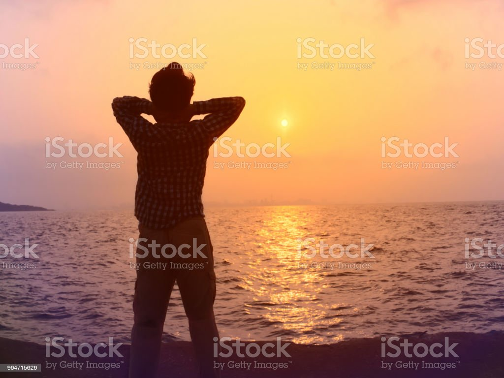 Back view of relaxed young Asian man standing with sunset background. royalty-free stock photo