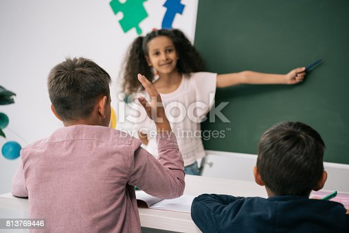 istock Back view of schoolboy raising hand and looking at smiling african american schoolgirl pointing at chalkboard 813769446