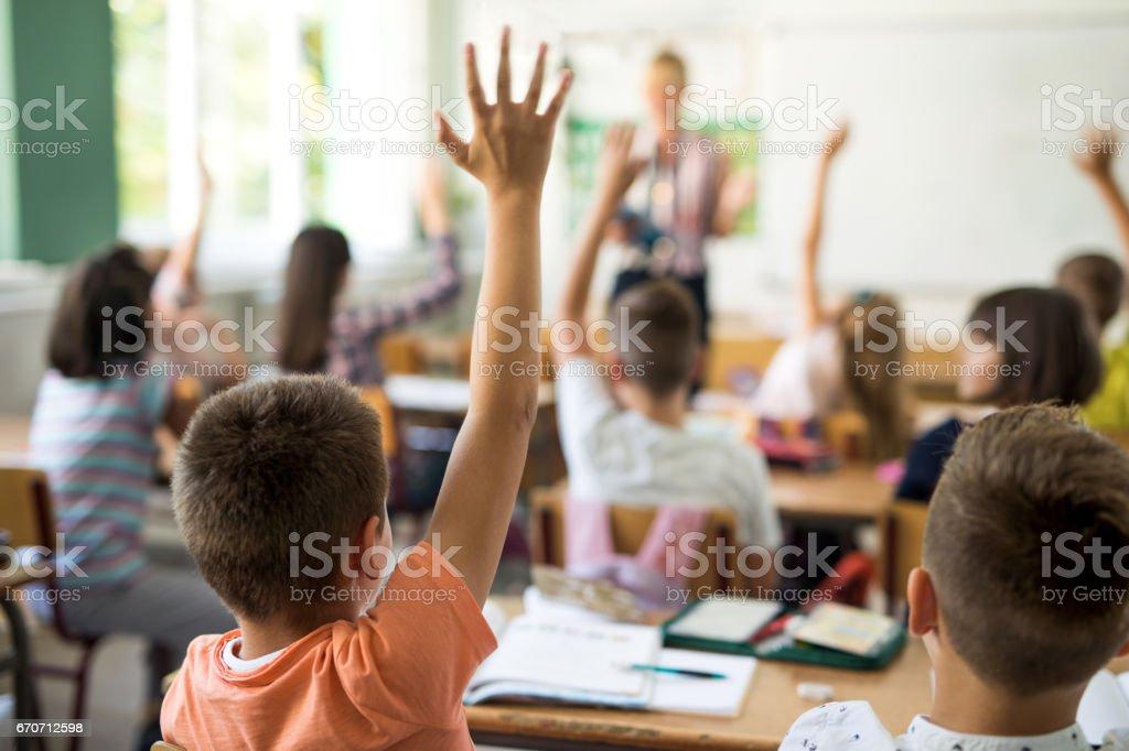 Vue d'écolier de lever la main pour répondre à la question de l'arrière. photo libre de droits