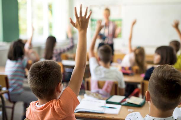 vista posterior de colegial levantando la mano para responder a la pregunta. - escuela primaria fotografías e imágenes de stock