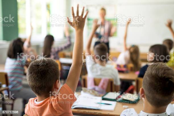 Rear view of little boy and his classmates raising arms to answer teacher's question during the lecture in the classroom.