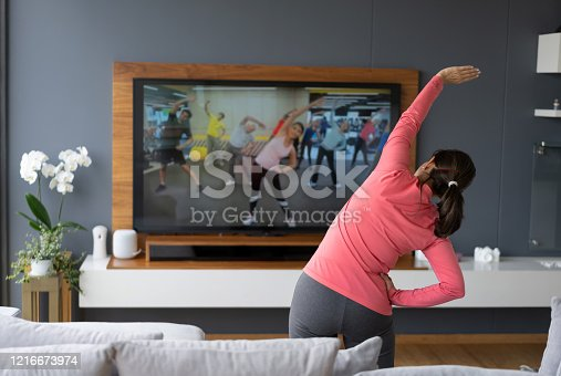 Back view of senior woman following an online stretching class looking at TV screen - Technology concepts. **IMAGE ON SCREEN BELONGS TO US**