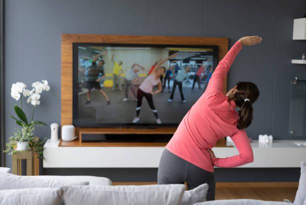 vista posterior de la mujer senior después de una clase de estiramiento en línea mirando la pantalla de la televisión - ejercicio físico fotografías e imágenes de stock