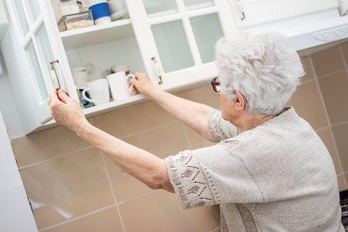 Back view of senior woman taking dishes from cupboard in the kitchen.