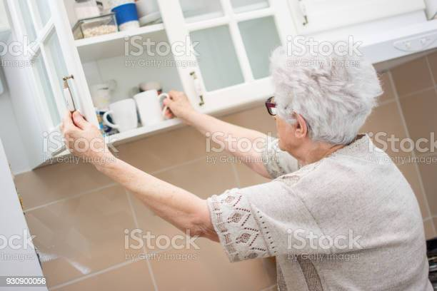 Back view of senior woman taking dishes from cupboard in the kitchen picture id930900056?b=1&k=6&m=930900056&s=612x612&h=mmbt0j5nu4ogiscw59wmtr8ce5aorltcldtosemqmuq=