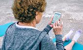istock Back view of senior woman using smartphone 828221504