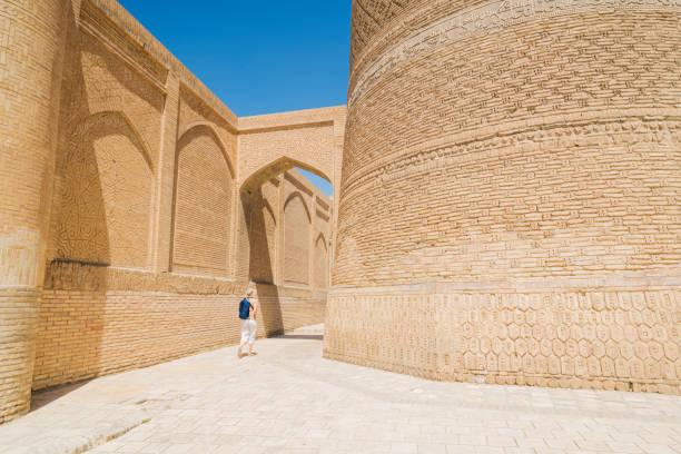 achteraanzicht van senior vrouwen wandelen naar het poi kalyan plein in buchara, uzbekusrtan - oezbekistan stockfoto's en -beelden