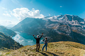 Beck view of Seniors, couple man with hands up and woman are enjoying beautiful view of lake Fedaia and Marmolada mountain while standing on resting point on path from Fedaia pass to pass Pordoi in Dolomites, Northern Italy, Europe. Marmolada is the highest mountain in Dolomites.