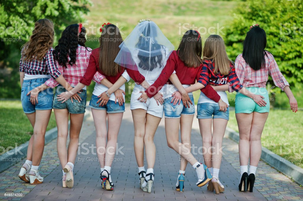 Back view of seven happy and sexy girls on short shorts holding hands on the buttocks and posed on road at park on bachelorette party - foto stock