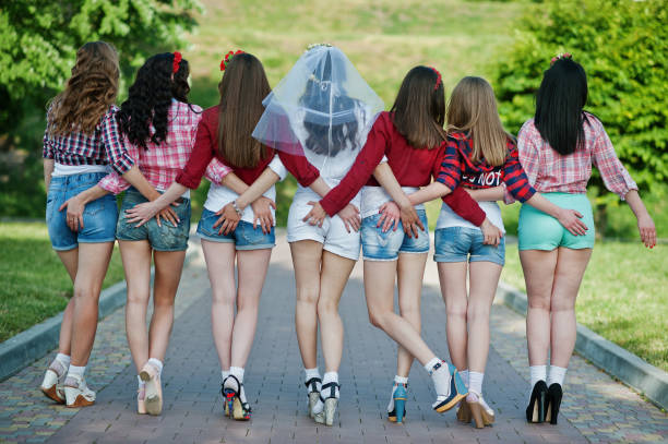 Back view of seven happy and sexy girls on short shorts holding hands on the buttocks and posed on road at park on bachelorette party stock photo
