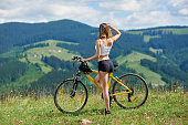 Back view of sexy sporty female biker standing with yellow mountain bicycle on a grass, enjoying summer day. Mountains, forests on the blurred background. Outdoor sport activity, lifestyle concept