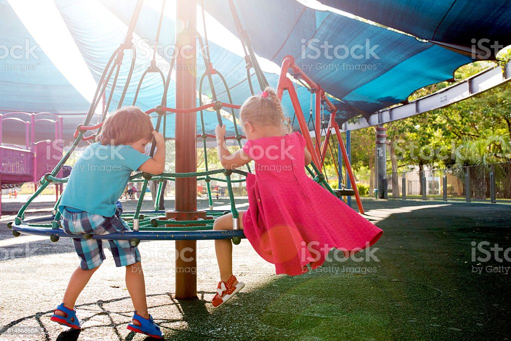 Back view of small kids playing at the playground. stock photo