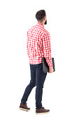 Back view of smart casual man with laptop walking and looking up watching copyspace. Full length isolated on white background.
