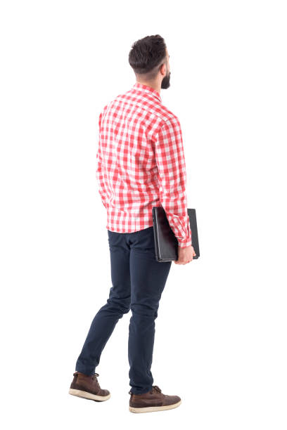 back view of smart casual man with laptop walking and looking up watching copyspace - guardare in su foto e immagini stock