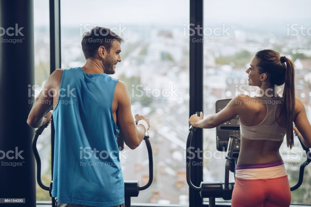 Back view of smiling athletic couple talking while exercising in a gym. royalty-free stock photo