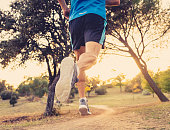 Back view of sport man with ripped athletic and muscular legs running off road in nature at autumn sunset in jogging training workout at countryside in fitness and healthy lifestyle concept.