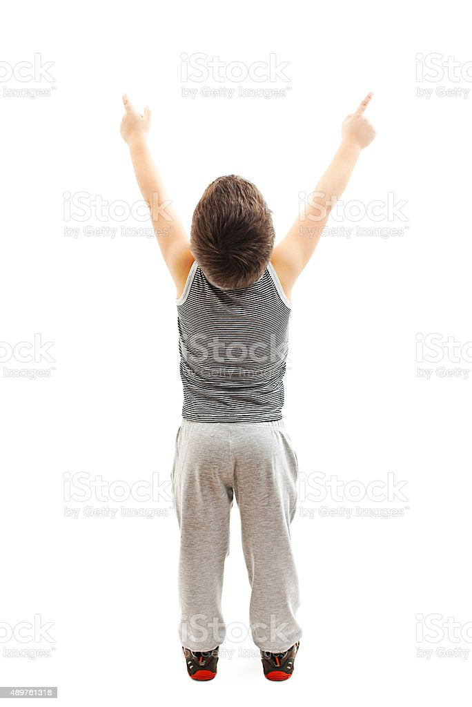 Back view of sporty little boy points at wall stock photo