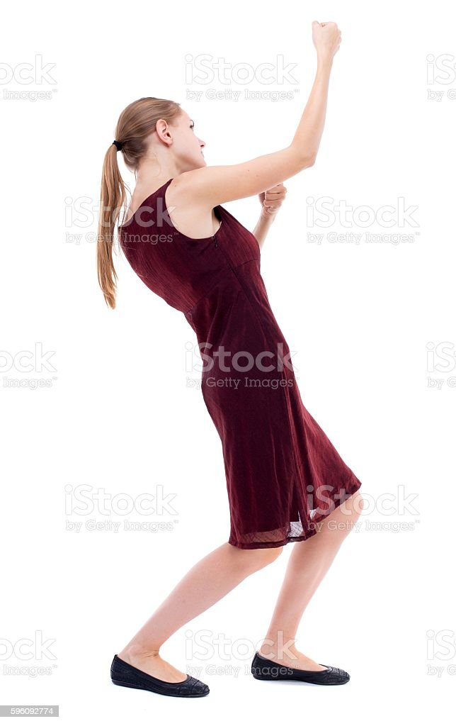 back view of standing girl pulling a rope from the royalty-free stock photo