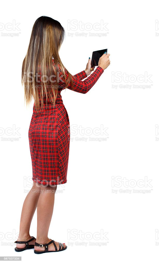back view of standing young beautiful  woman  and using a stock photo