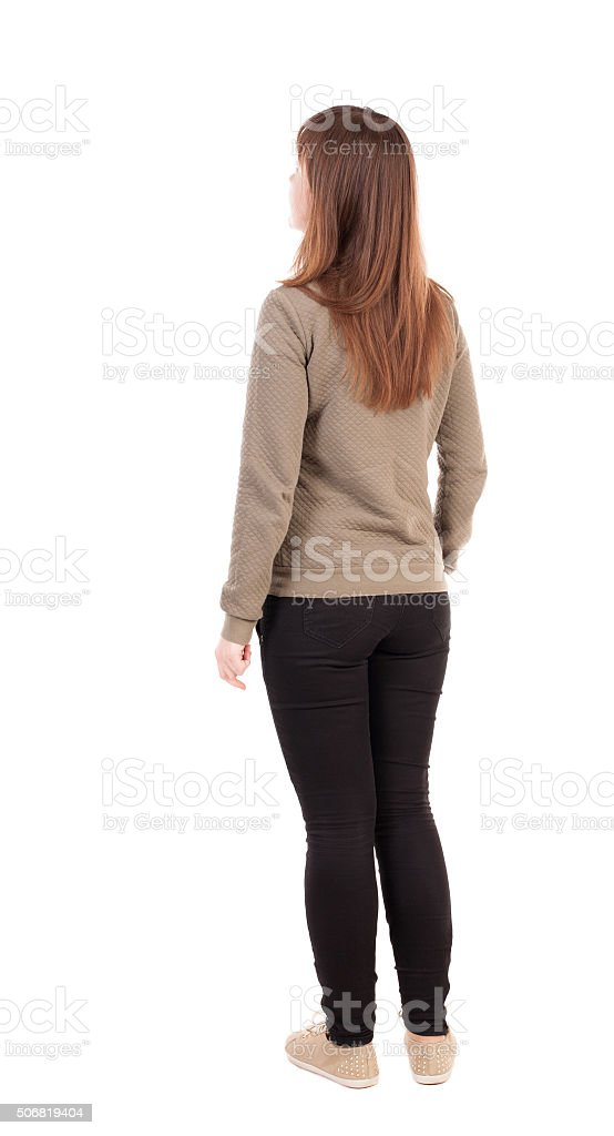 back view of standing young beautiful  woman in jeans. stock photo