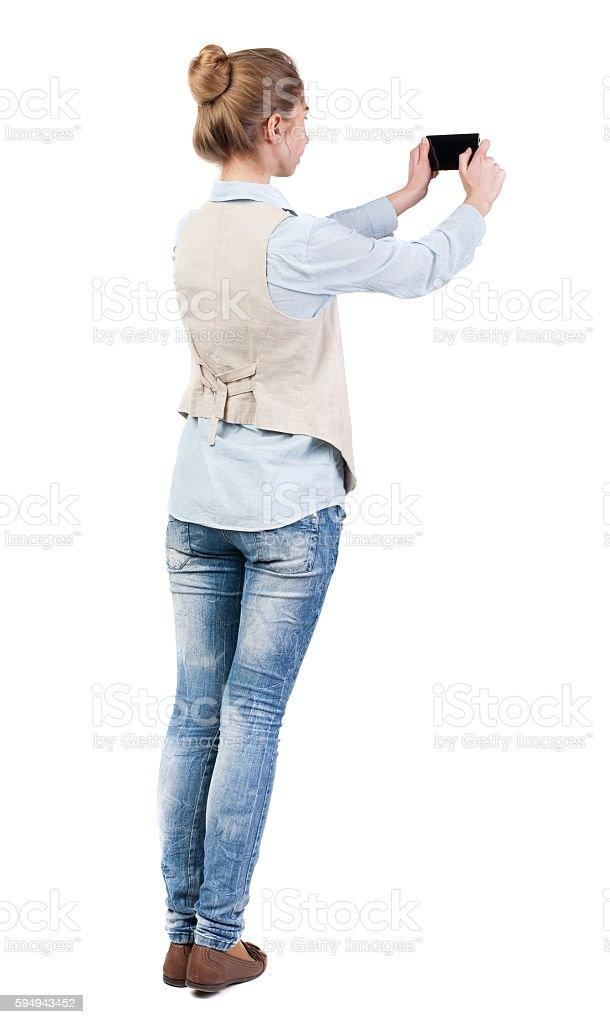 back view of standing young beautiful  woman  in vest and stock photo
