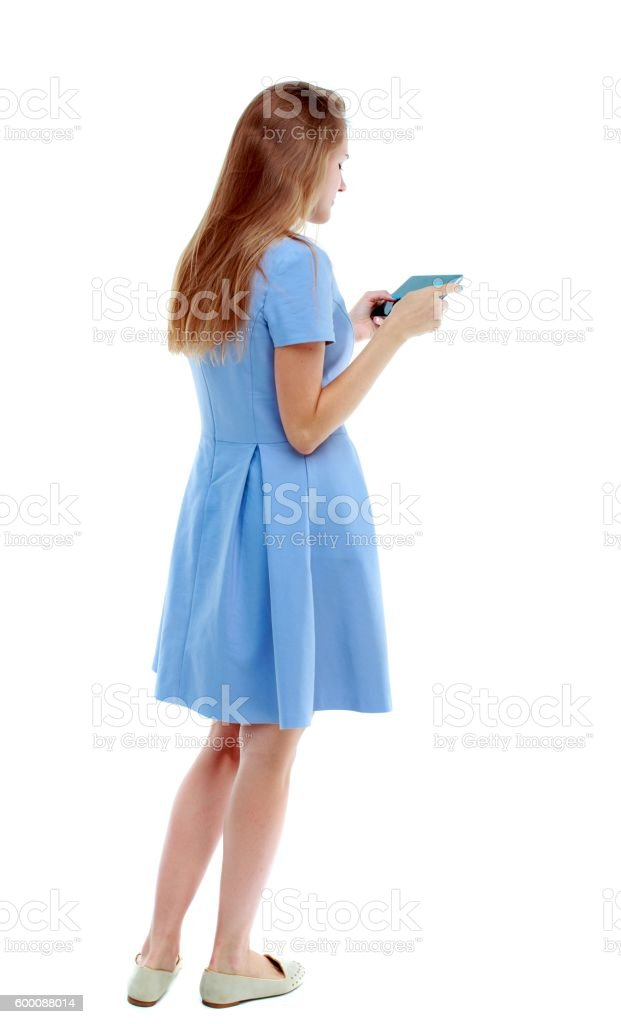 back view of standing young beautiful  woman using a mobile stock photo