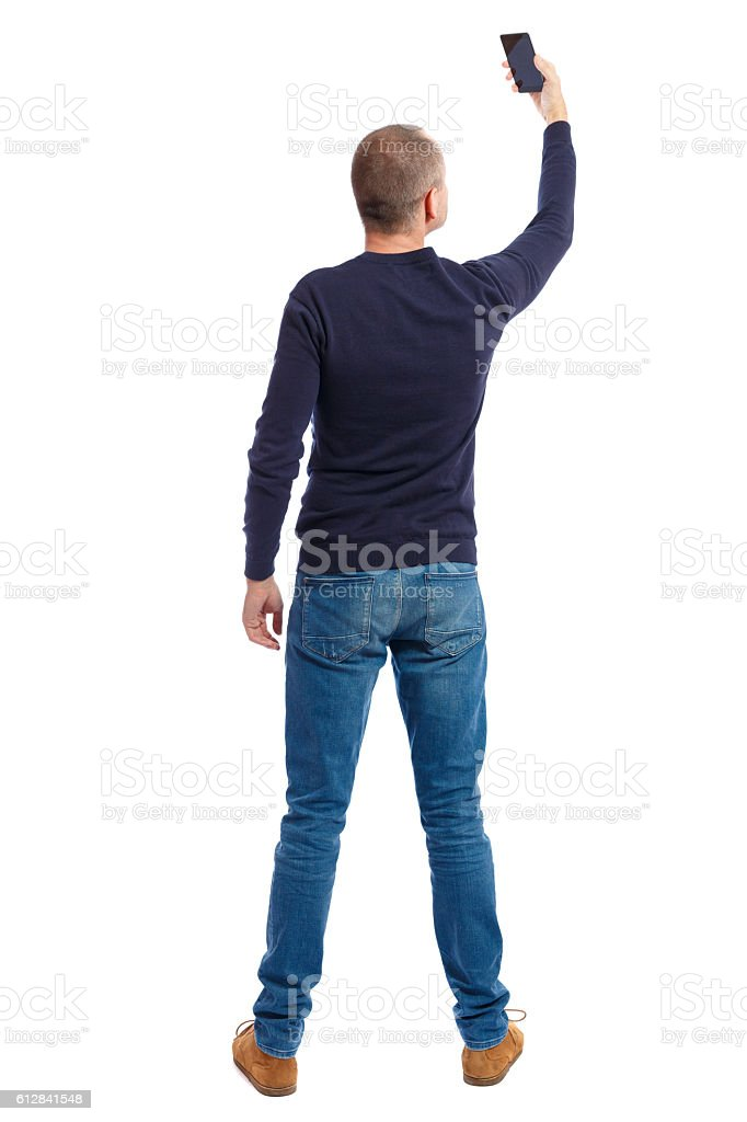 back view of standing young man and using a mobile stock photo