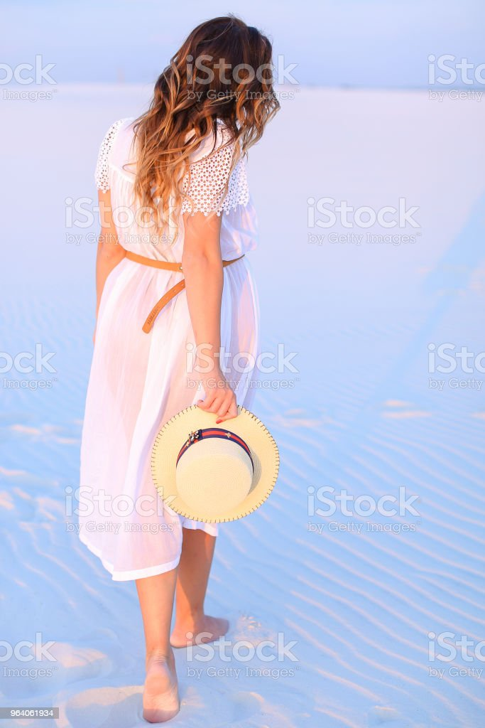 Back view of standing young woman on white blue sand - Royalty-free Adult Stock Photo