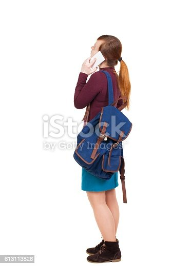 istock Back view of standing young woman with backpack speaks by 613113826