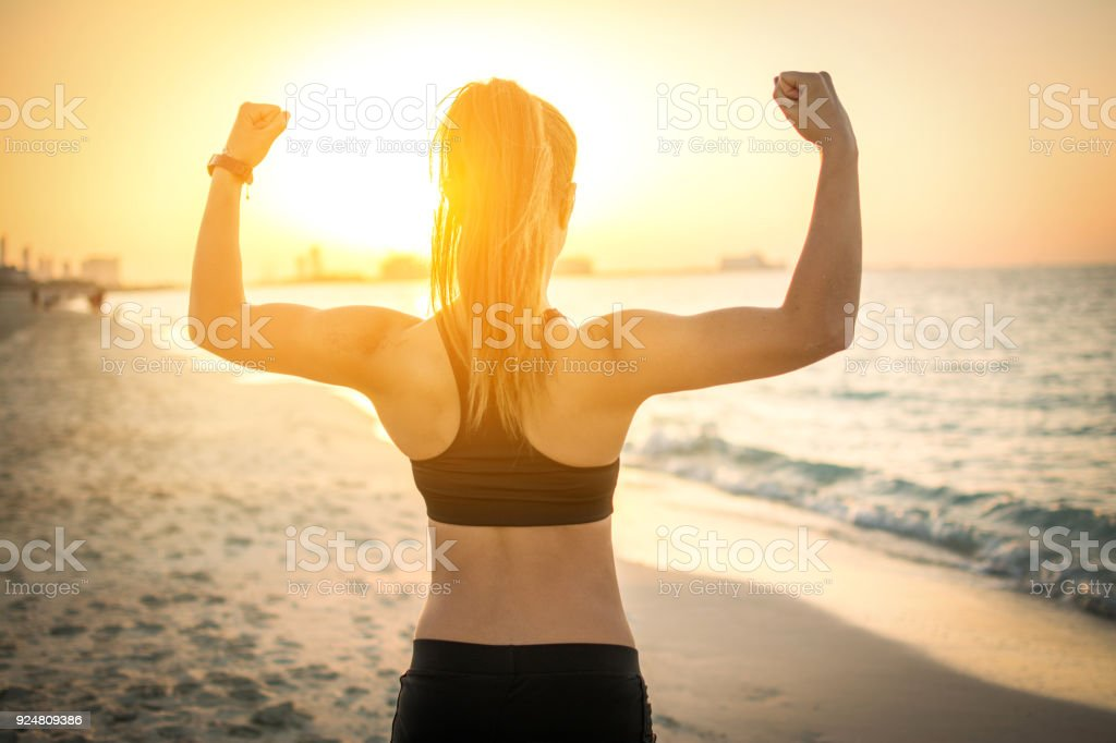 Rückansicht des starken sportliches Girl zeigt Muskeln am Strand bei Sonnenuntergang. - Lizenzfrei Aktiver Lebensstil Stock-Foto