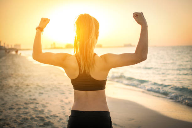 Back view of strong sporty girl showing muscles at the beach during sunset. stock photo