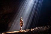 Rear view of woman standing in the cave and looking at sunlight entering. Copy space.