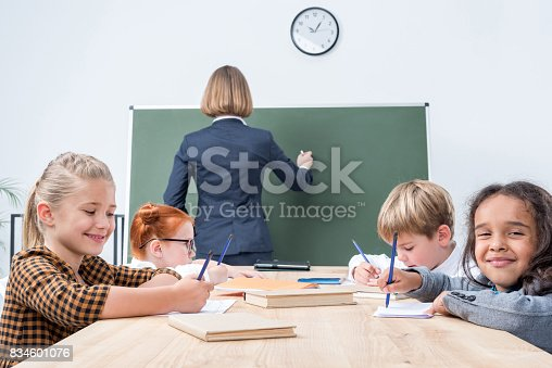 istock back view of teacher writing on chalkboard while students studying in classroom 834601076