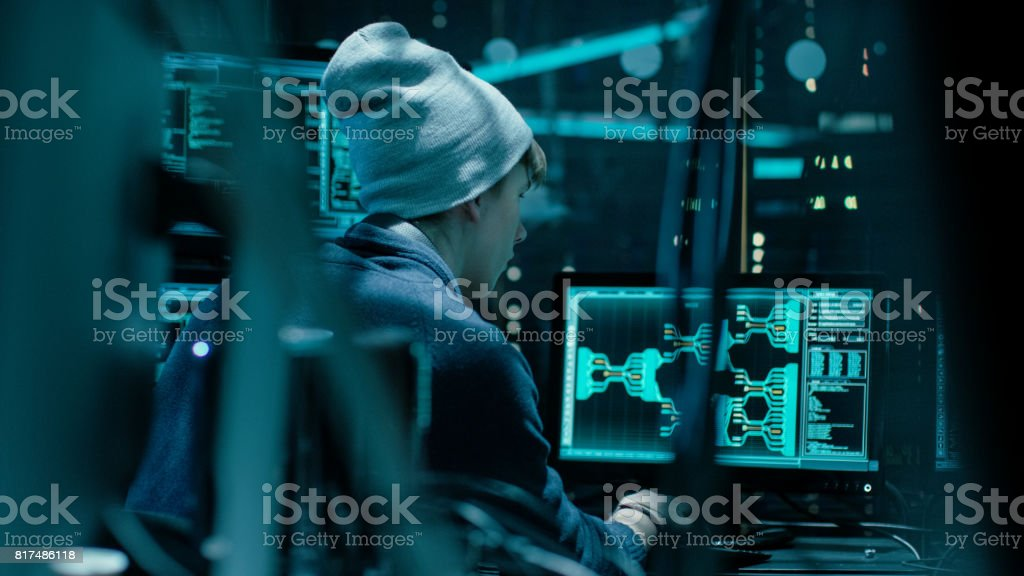 Back View of Teenage Hacker Working in Computer and Infecting with Virus Data Servers of Government Infrastructures. His Hideout is Dark with Many Monitors Around. stock photo
