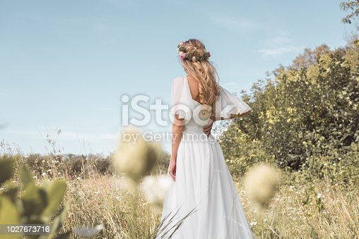 back view of tender young blonde bride walking on beautiful field