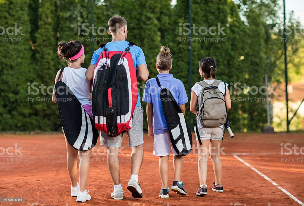 Back view of tennis coach walking with group of children. stock photo
