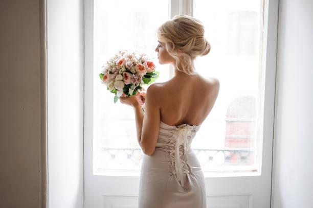 widok z tyłu eleganckiej blondynki panny młodej ubranej w białą sukienkę trzymającą bukiet ślubny - panna młoda zdjęcia i obrazy z banku zdjęć