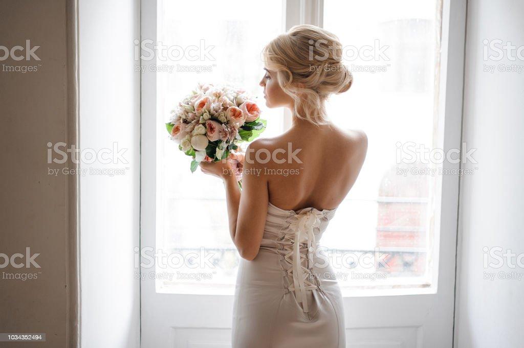 Rückansicht der elegante blonde Braut gekleidet in einem weißen Kleid hält ein Brautstrauß – Foto