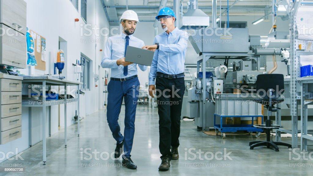 Rückansicht des Leiters des Projekts hält Laptop und diskutieren Produktdetails mit Chief Engineer während sie spazieren durch die moderne Fabrik. – Foto