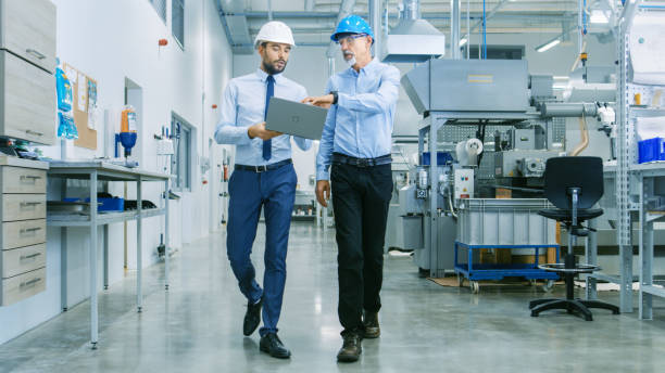 Back View of the Head of the Project Holds Laptop and Discussing Product Details with Chief Engineer while They Walk Through Modern Factory. stock photo