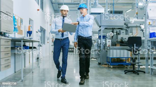 Back View Of The Head Of The Project Holds Laptop And Discussing Product Details With Chief Engineer While They Walk Through Modern Factory Stock Photo - Download Image Now
