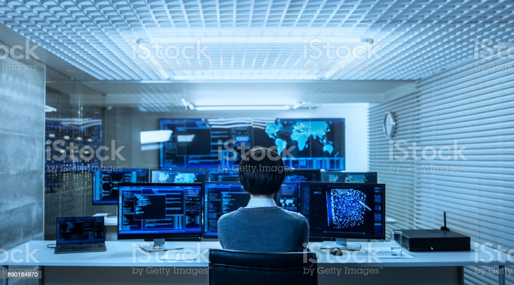 Back View of the IT Engineer Working with Multiple Monitors Showing Graphics, Functional Neural Network. He Works in a Technologically Advanced System Control Data Center. - Royalty-free Administrator Stock Photo
