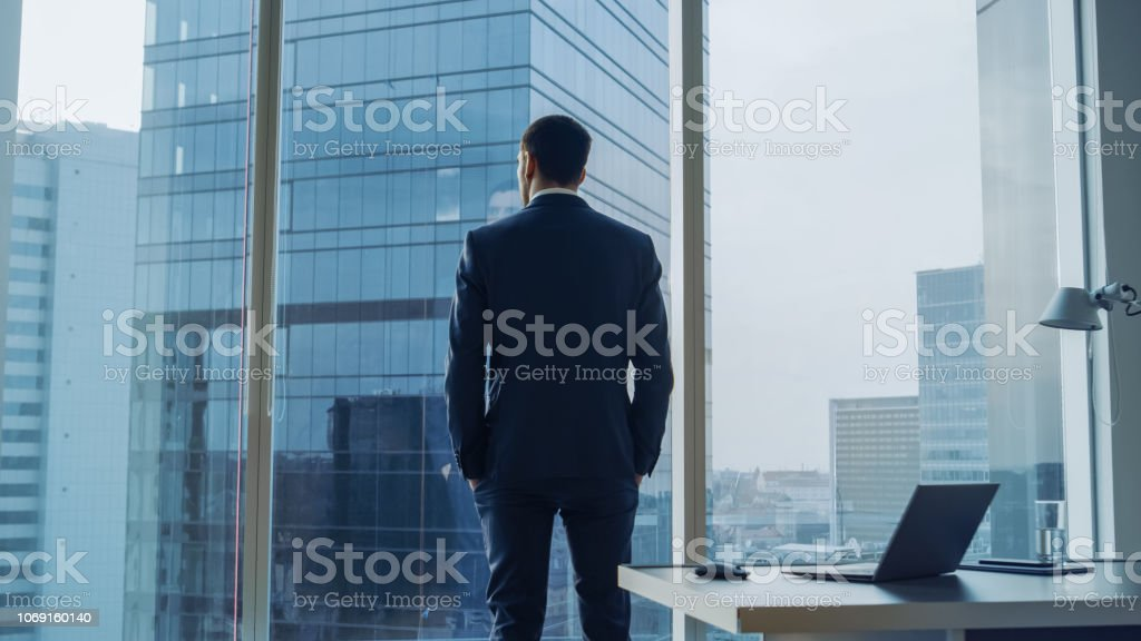 Back View of the Thoughtful Businessman wearing a Suit Standing in His Office, Hands in Pockets and Contemplating Next Big Business Deal, Looking out of the Window. Big City Business District Panoramic Window View. Back View of the Thoughtful Businessman wearing a Suit Standing in His Office, Hands in Pockets and Contemplating Next Big Business Deal, Looking out of the Window. Big City Business District Panoramic Window View. Achievement Stock Photo